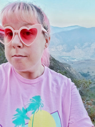 pink haired woman with heart sunglasses posing in front of a canyon.