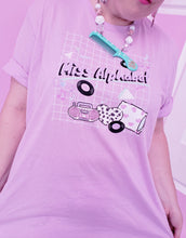 Load image into Gallery viewer, woman modeling t-shirt with miss alphabet logo, pillows, and pink 90s barbie boombox print