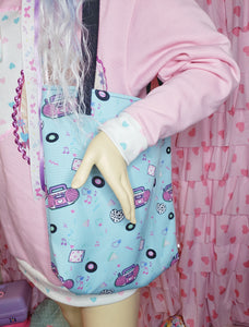 blue tote bag with pink boomboxes, modeled on a mannequin wearing a pink sweater