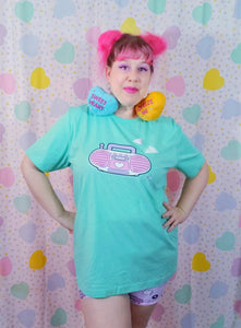 woman wearing mint green t-shirt with pink barbie boombox