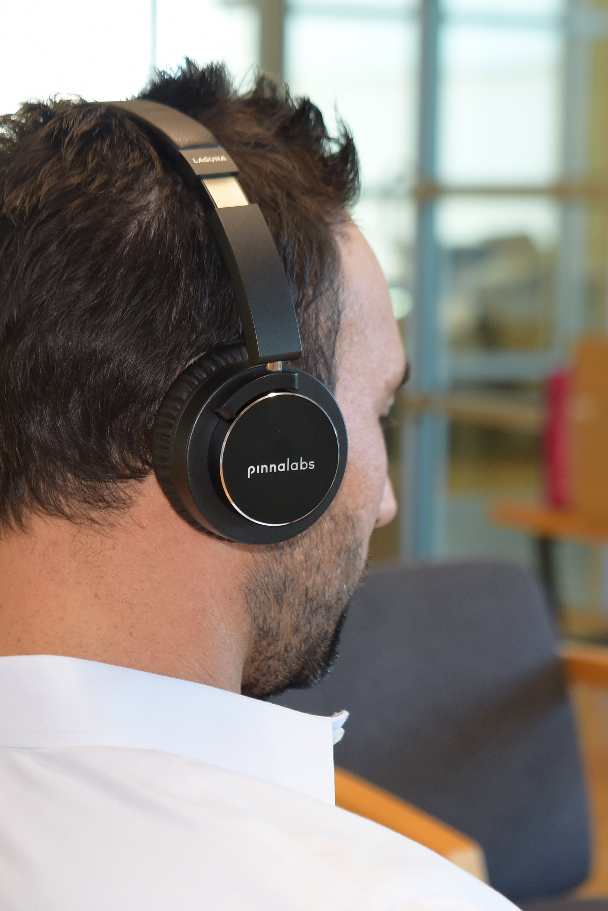 Man listens to Pinna Labs' LAGUNA Safe Volume headphone in office.