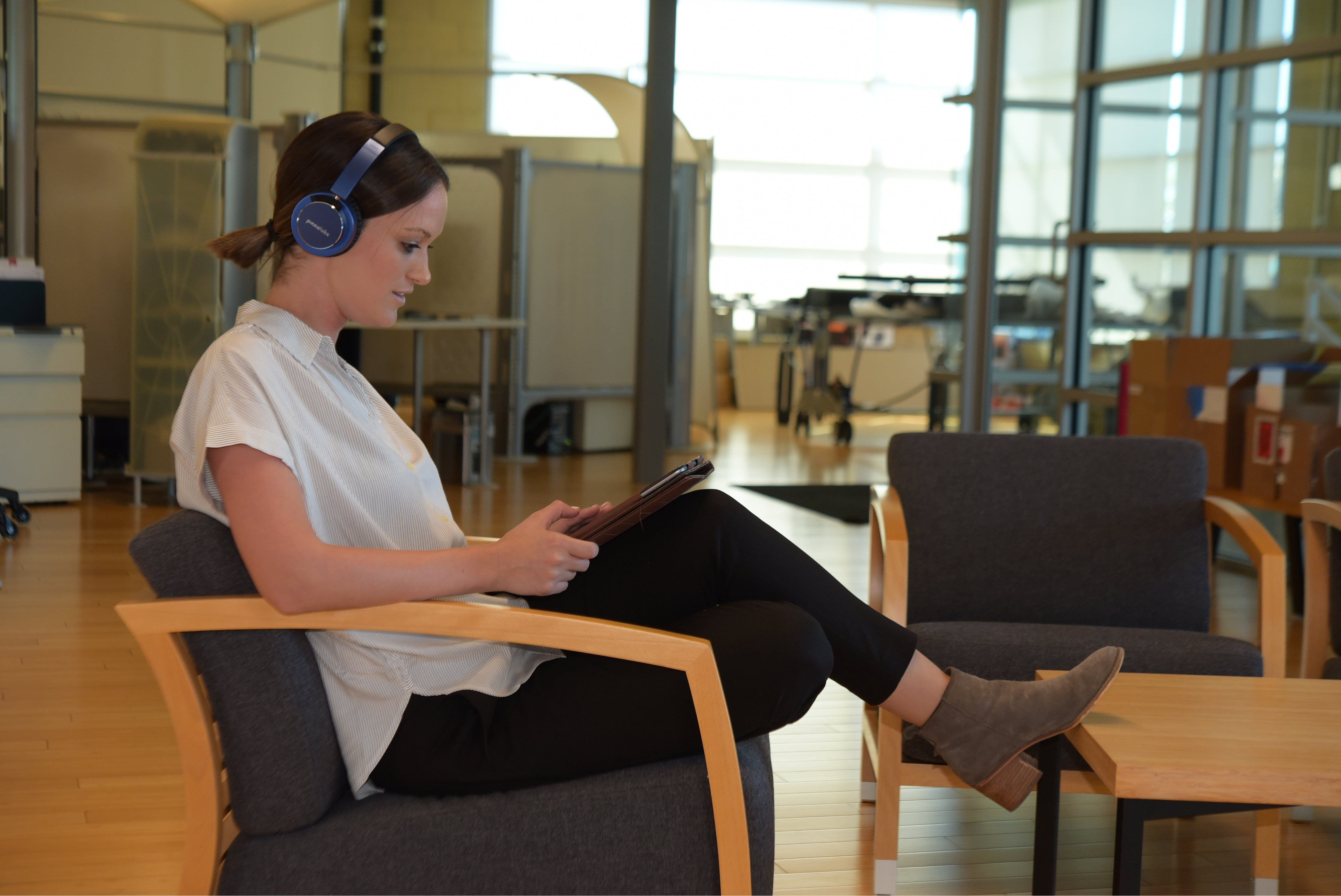 Woman in office listens to Pinna Labs' LAGUNA safe volume headphone for adults.