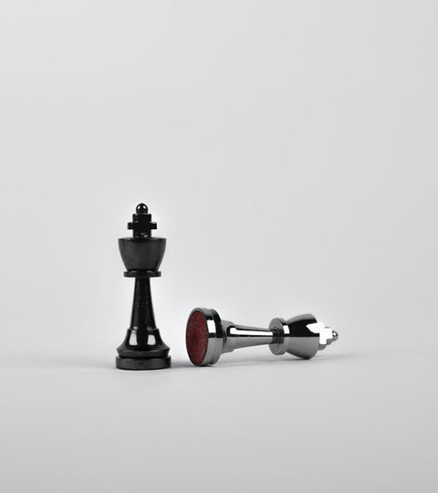 two chess pieces, one silver and one black, with the silver one knocked over
