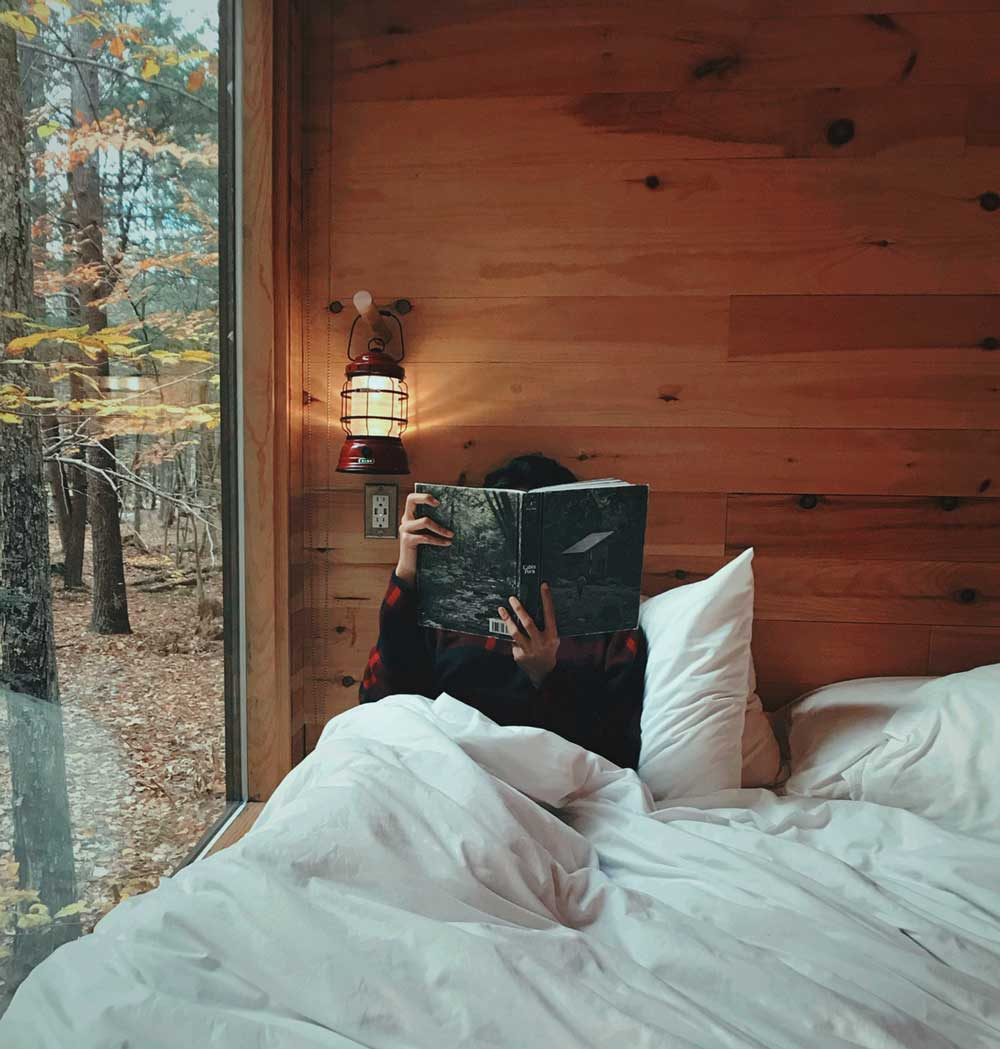 person sitting in bed reading a book