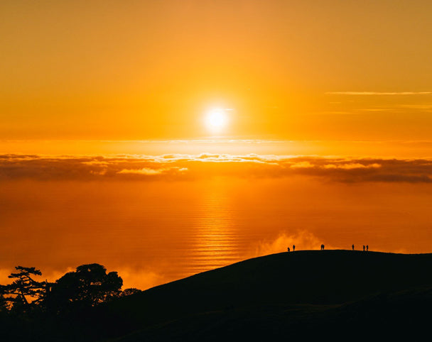 the sun over water with a hill