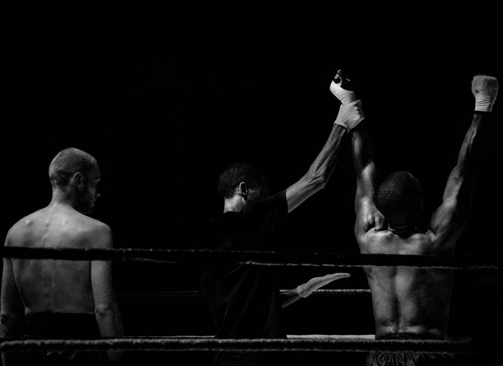 black and white image of two boxers in a ring, one with his hand lifted as the winner