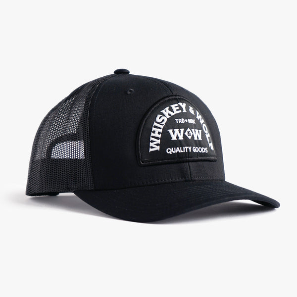 Heritage trucker cap in balck with curved front brim designed by whiskey and wolf supply co