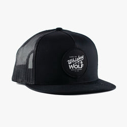 flat brim trucker cap with whiskey and wolf supply co circular patch on front of hat