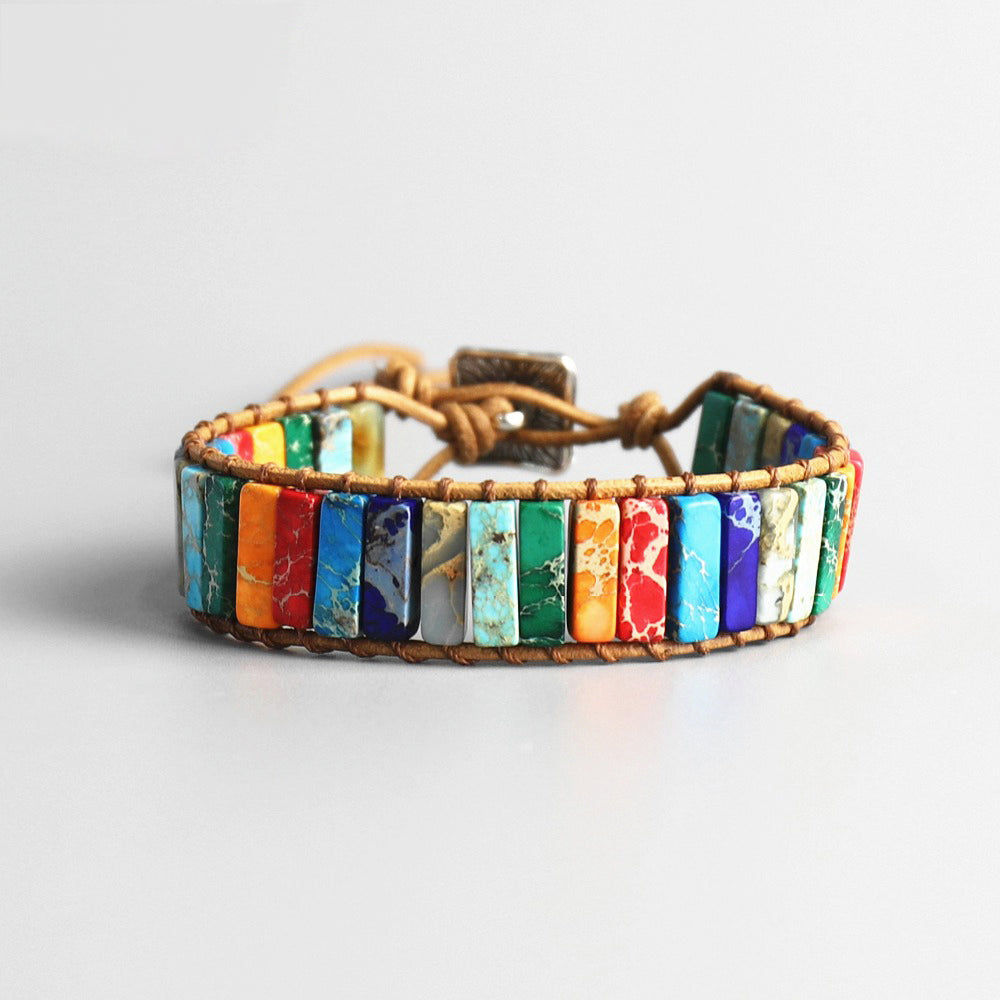 A chakra stone bracelet with various rectangle stones in sky blue, white, purple, red, orange, emerald green, turquoise, grey, dark blue, linked with a leather-looking rope and a square metal plate