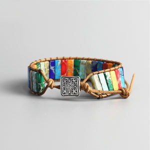 A chakra stone bracelet from the back with various rectangle stones in sky blue, white, purple, red, orange, emerald green, turquoise, grey, dark blue, linked with a leather-looking rope and a square metal plate