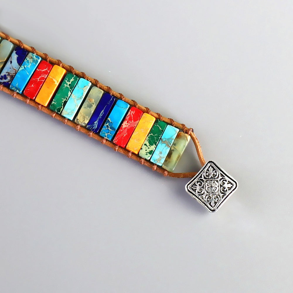 An open chakra stone bracelet with various rectangle stones in sky blue, white, purple, red, orange, emerald green, turquoise, grey, dark blue, linked with a leather-looking rope and a square metal plate