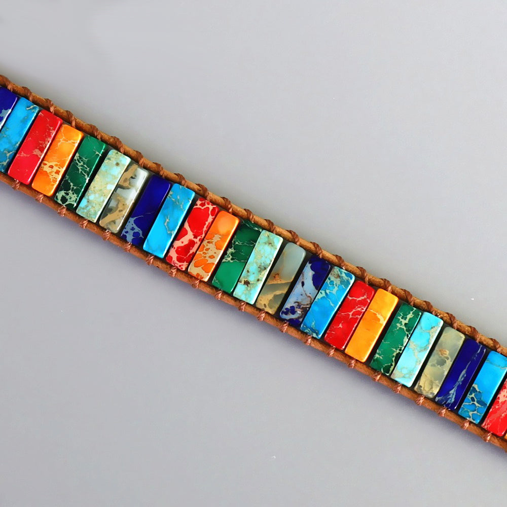 An open chakra stone bracelet with various rectangle stones in sky blue, white, purple, red, orange, emerald green, turquoise, grey, dark blue, linked with a leather-looking rope