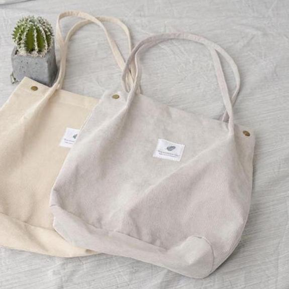 "Beige and grey corduroy bag with a white square fabric with a feather and the sentence ""you need this one"""
