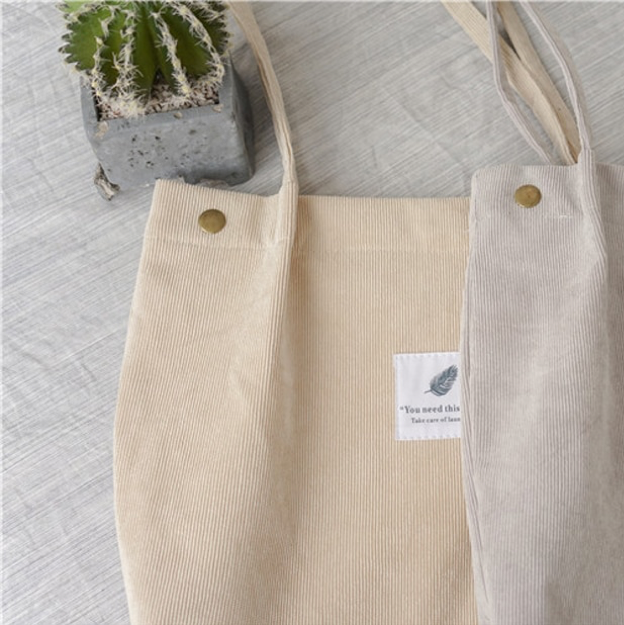 "Beige corduroy bag with a white square fabric with a feather and the sentence ""you need this one"""