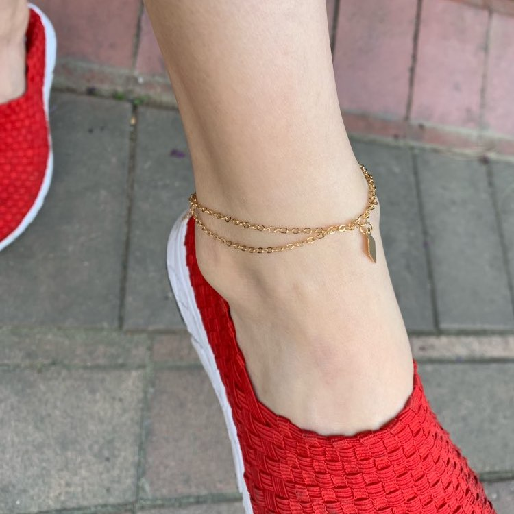 A doubled golden anklet with a golden diamond shape plate worn in an ankle with red shoes