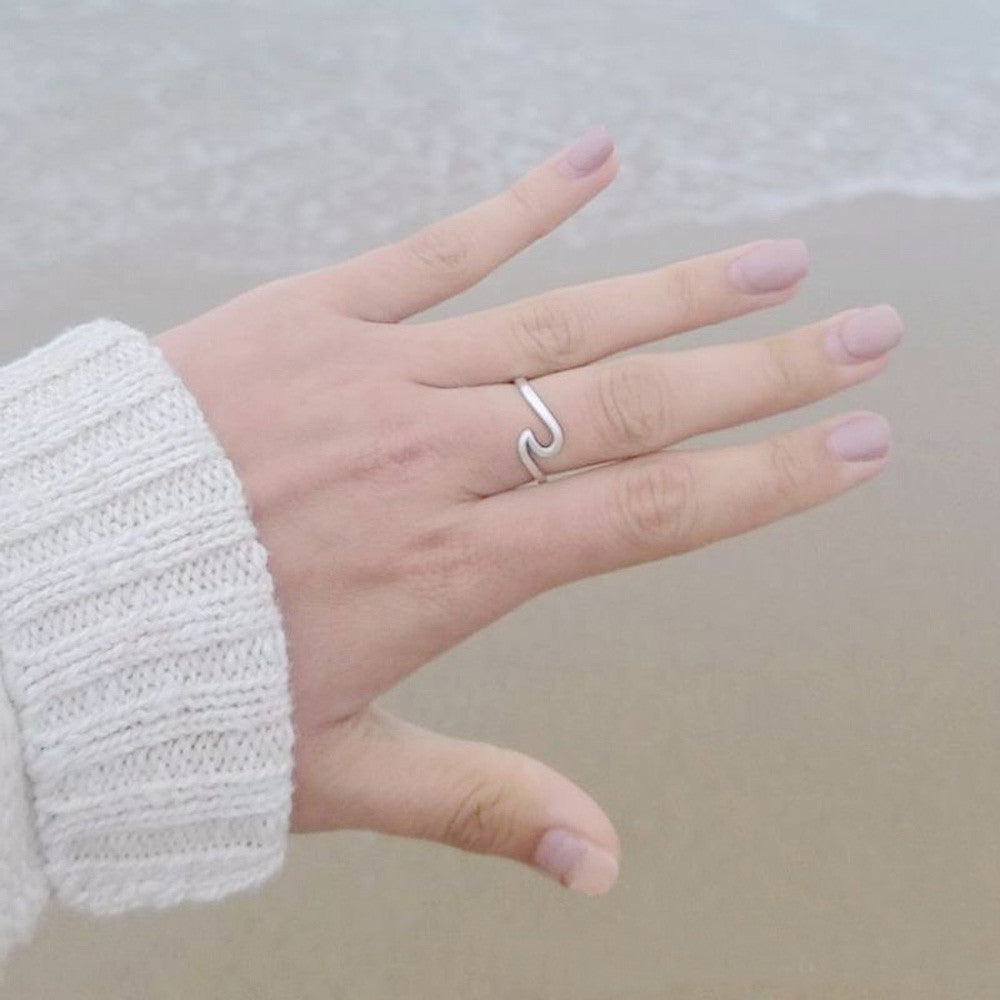 Silver wave shaped ring in a hand