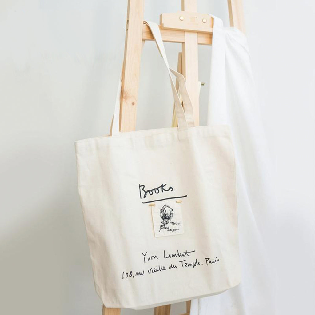 Cream white tote bag with letters and a white fabric detail, hang on a canvas holder
