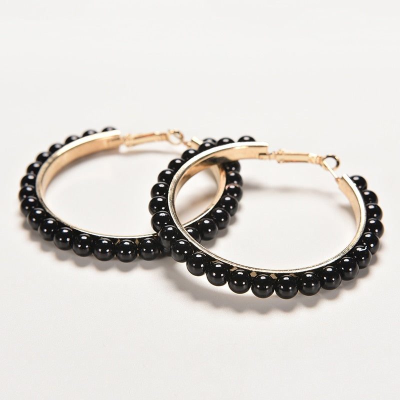 Set of golden hoops earrings with pearls in black