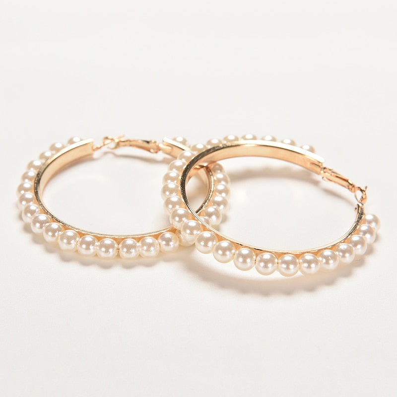 Set of golden hoops earrings with pearls in white