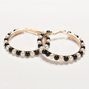 Set of golden hoops earrings with pearls in white and black