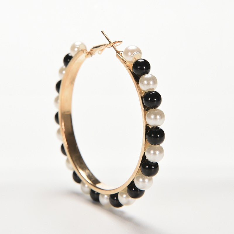 One golden hoop earring with pearls in black and white