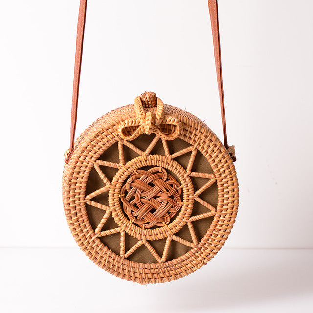 Circle light brown straw bag with edges and a sun-like pattern in the middle and a small bow buckle lock