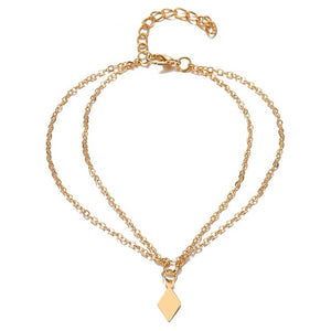A doubled golden anklet with a golden diamond shape plate