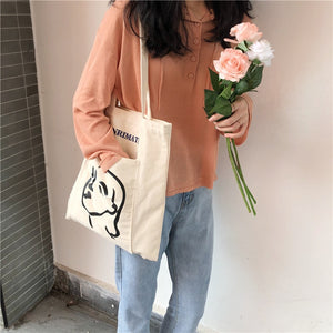 Woman carrying cream white tote bag with an artsy sketch of a woman's face in black