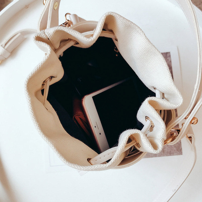 White hand bag with long and short straps. Striped with white and transparent and a removable inner white pouch, view from the top