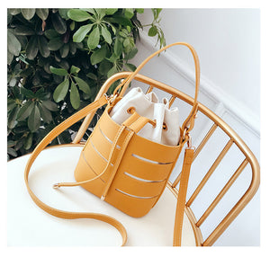 Yellow hand bag with long and short straps. Striped with white and transparent and a removable inner white pouch