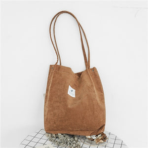 "Brown corduroy bag with a white square fabric with a feather and the sentence ""you need this one"""