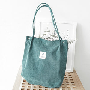 "Green corduroy bag with a white square fabric with a feather and the sentence ""you need this one"""