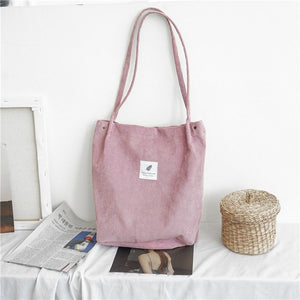 "Pink corduroy bag with a white square fabric with a feather and the sentence ""you need this one"""