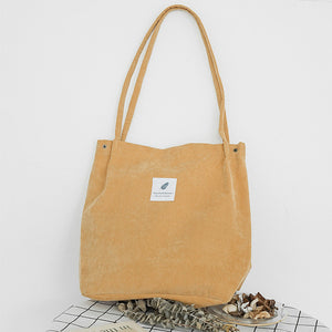 "Yellow corduroy bag with a white square fabric with a feather and the sentence ""you need this one"""