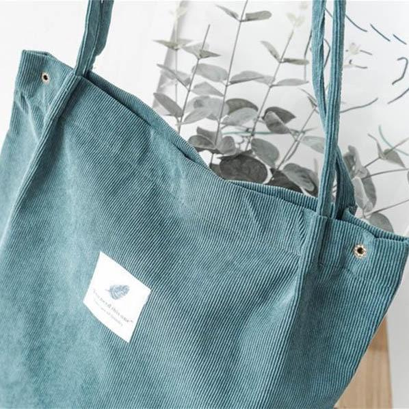 "Zoomed green corduroy bag with a white square fabric with a feather and the sentence ""you need this one"""