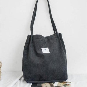 "Black corduroy bag with a white square fabric with a feather and the sentence ""you need this one"""