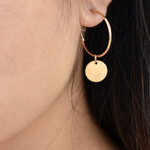 Golden hoop earrings with a hang golden coin