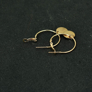 Golden hoop earrings with a hang golden coin opened and put on a black background