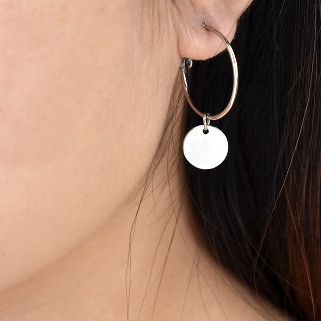 Silver color hoop earrings with a hang golden coin
