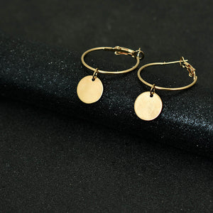 Golden hoop earrings with a hang golden coin put on a black background