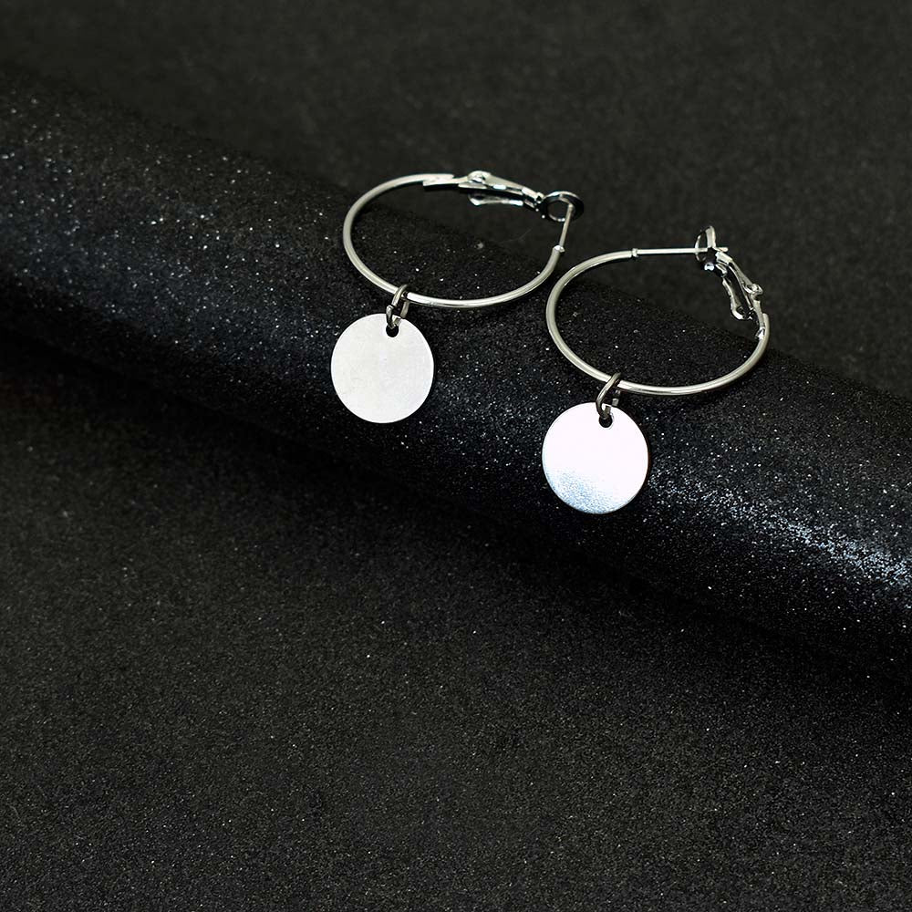 Silver colored hoop earrings with a hang golden coin put on a black background