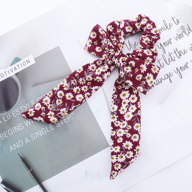 A burgundy red ribbon and bow hair tie with white daisy flowers