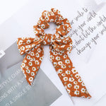 A rusty orange ribbon and bow hair tie with white daisy flowers