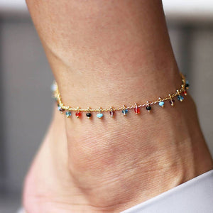 Golden anklet with small beads in purple, blue, red, black and sky blue