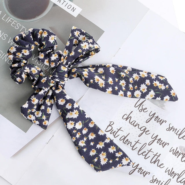 A dark blue ribbon and bow hair tie with white daisy flowers