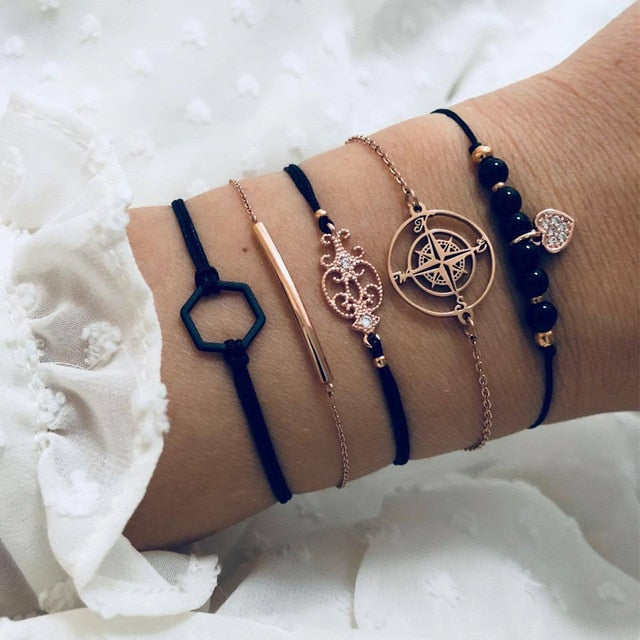 Dark blue bracelet set with a dark hexagon, a thin rectangle golden metal plate, a baroque-style golden metal, a golden compass and a heart