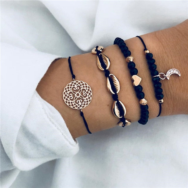 Dark blue bracelet set with a golden metal mandala, golden metal puka shells, a golden metal heart and a moon