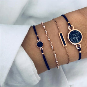 Dark blue bracelet set with a small dark stone, small golden metal beads, a dark stone rectangle with golden metal and a big blue marble circle stone with golden metal