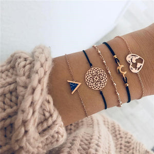 Bracelet set with a blue marble triangle with golden metal borders, a golden metal mandala, small golden metal beads, a golden moon and a golden heart-shaped earth