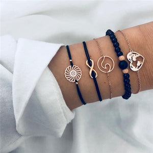 Bracelet set with a golden metal flower, a golden metal infinity sign, a golden metal circle with a wave, a big black bead with two golden beads on the side and a golden metal heart-shaped earth